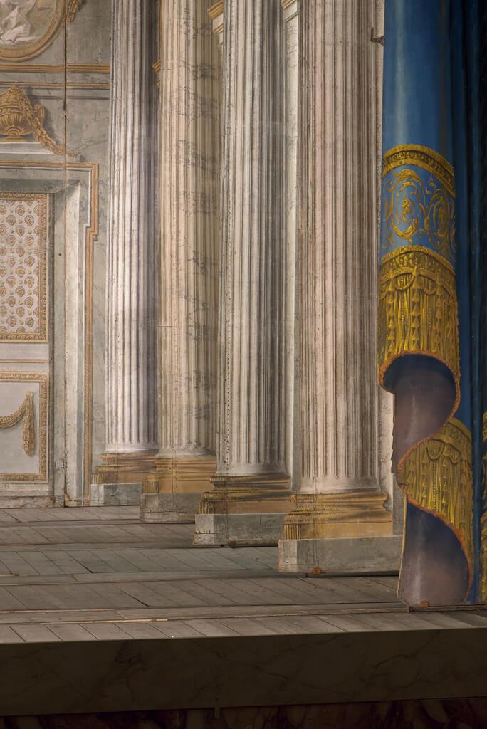 Détail du décor de scène du Temple de Minerve: «… colonnes cannelées, ton de marbre blanc, ornements rehaussés d'or» vus du côté cour. © Château de Versailles / Thomas Garnier.