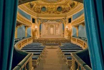 Intérieur du Petit Théâtre de laReine: vue sur lasalle avec lumière ambiante; en fond, décor de scène duTemple deMinerve, par les frères Slodtz (1754).   © Château de Versailles / Thomas Garnier.